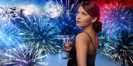 celebration event: party, drinks, holidays, luxury and celebration concept - smiling woman in evening dress holding cocktail over nigh city and firework background