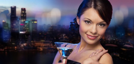 asian style: party, drinks, holidays, luxury and celebration concept - smiling woman in evening dress holding cocktail over night city background