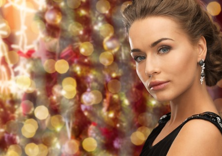 glamour woman: people, holidays, jewelry and glamour concept - beautiful woman wearing earrings over christmas lights background Stock Photo