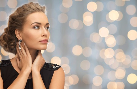 people, holidays and glamour concept - beautiful woman wearing earrings over lights background