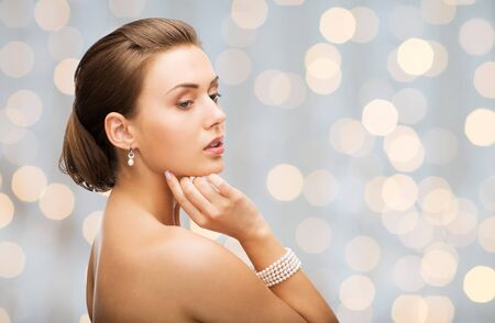jewel hands: beauty, luxury, people, holidays and jewelry concept - beautiful woman with pearl earrings and bracelet over lights background