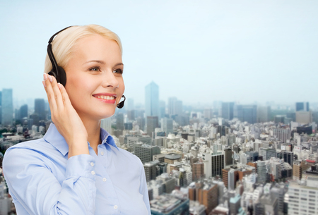 helpline: business, people, technology and communication concept - happy female helpline operator in headset over city background Stock Photo