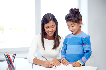 asian mother and daughter: family, children, creativity and happy people concept - happy mother and daughter drawing with pencils at home or kindergarten
