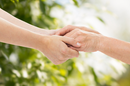 female hand: people, age, family, care and support concept - close up of senior woman and young woman holding hands over green natural background