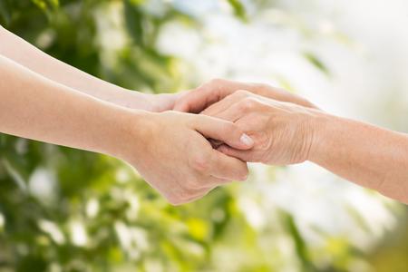 persone, età, famiglia, assistenza e sostegno concetto - vicino di donna senior e giovani mani della holding della donna su sfondo verde naturale