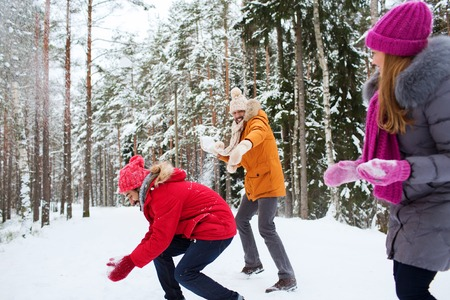 winter fashion: christmas, season, friendship and people concept - group of smiling men and women having fun and playing snowball game in winter forest