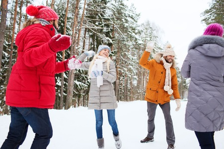 cold war: christmas, season, friendship and people concept - group of smiling men and women having fun and playing snowball game in winter forest
