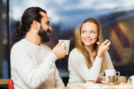winter girl: people, leisure and communication concept - happy couple meeting and drinking tea or coffee at cafe