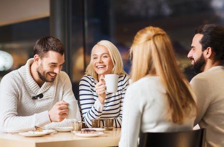 amicizia: persone, il tempo libero e il concetto di comunicazione - gli amici felici che soddisfano e che bevono tè o caffè al bar