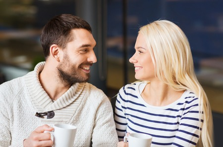 people, leisure and communication concept - happy couple meeting and drinking tea or coffee at cafe