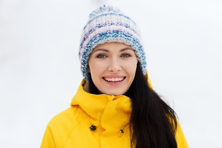 clothes: winter, leisure, clothing and people concept - happy young woman in winter clothes outdoors