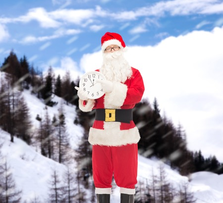 12 oclock: christmas, holidays and people concept - man in costume of santa claus with clock showing twelve pointing finger over snowy mountains background