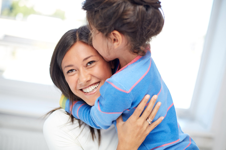 asian child: family, children, love and happy people concept - happy mother and daughter hugging at home Stock Photo