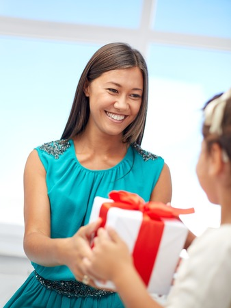 receiving: holidays, birthday family, childhood and people concept - happy mother giving present to her daughter at home