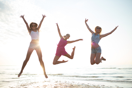 jump: friendship, summer vacation, freedom, happiness and people concept - group of happy female friends dancing and jumping on beach Stock Photo