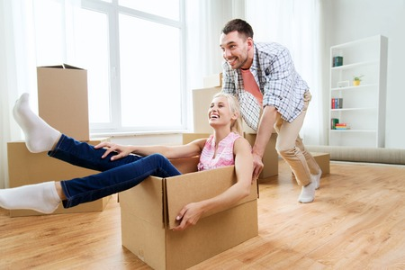 people moving: home, people, moving and real estate concept - happy couple having fun and riding in cardboard boxes at new home