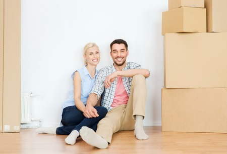 moving in: home, people, repair, moving and real estate concept - happy couple with many cardboard boxes sitting on floor at new place Stock Photo