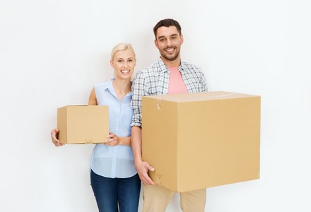 home, people, repair and real estate concept - happy couple holding cardboard boxes and moving to new place Imagens