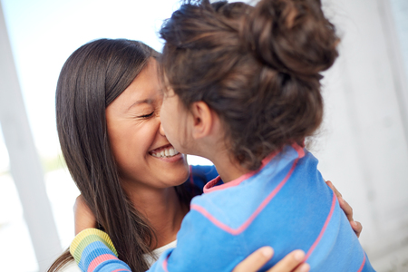 preteen asian: family, children, love and happy people concept - happy little girl hugging mother and kissing her on nose at home Stock Photo