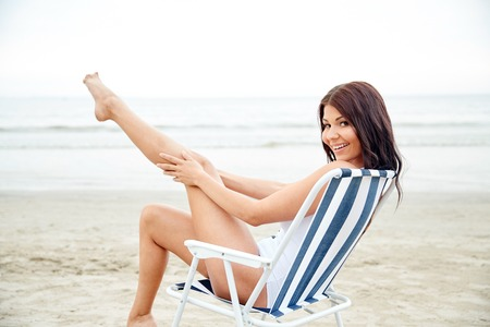 summer vacation, tourism, travel, holidays and people concept - smiling young woman sunbathing in lounge or folding chair on beach