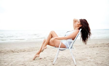 folding chair: summer vacation, tourism, travel, holidays and people concept - happy young woman sunbathing in lounge or folding chair on beach
