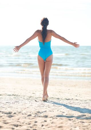 summer beach: summer vacation, tourism, travel, holidays and people concept -young woman in swimsuit posing on beach from back Stock Photo
