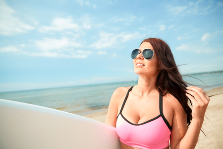 big breast woman: summer vacation, travel, surfing, water sport and people concept - young woman in swimsuit with surfboard on beach Stock Photo