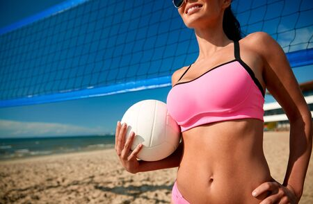 summer vacation, sport and people concept - close up of young woman with volleyball ball and net on beach Stock Photo