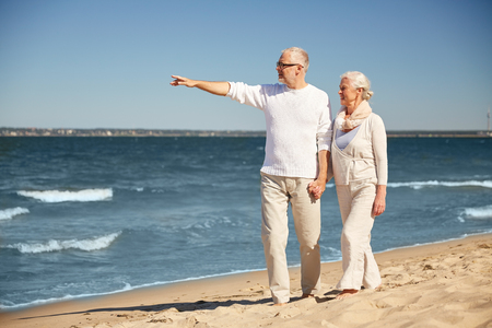 old couple walking: family, age, travel, tourism and people concept - happy senior couple walking and pointing finger to something on summer beach