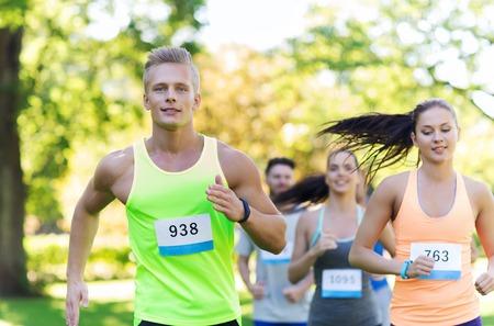 fitness, sport, vriendschap, ras en gezonde levensstijl concept - groep van gelukkige tiener vrienden of sporters loopt marathon met kenteken nummers buiten Stockfoto