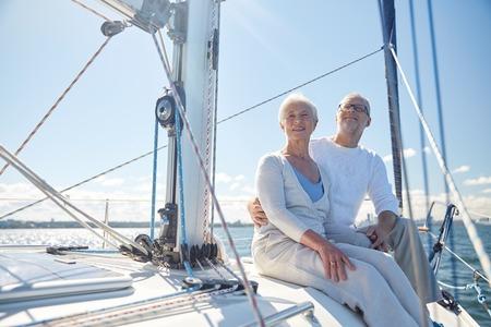 la vela, la edad, el turismo, los viajes y el concepto de la gente - feliz pareja de ancianos abrazando en barco de vela o la cubierta del yate flotando en el mar