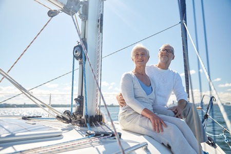 boat: sailing, age, tourism, travel and people concept - happy senior couple hugging on sail boat or yacht deck floating in sea