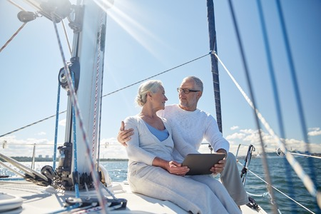 old couple: sailing, technology, tourism, travel and people concept - happy senior couple with tablet pc computer talking on sail boat or yacht deck floating in sea