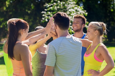 fitness, sport, friendship and healthy lifestyle concept - group of happy teenage friends or sportsmen making high five outdoors Banco de Imagens