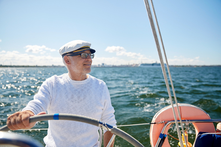 sailboat: sailing, age, tourism, travel and people concept - happy senior man in captain hat on steering wheel and navigating sail boat or yacht floating in sea