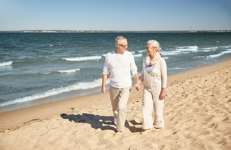 old couple walking: family, age, travel, tourism and people concept - happy senior couple walking along summer beach