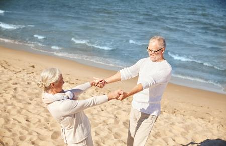 cogidos de la mano: familiar, la edad, los viajes, el turismo y el concepto de la gente - Pareja feliz celebración de las manos en alto la playa del verano