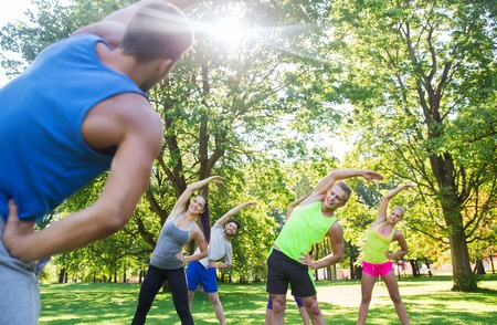 sportsmen: fitness, sport, friendship and healthy lifestyle concept - group of happy teenage friends or sportsmen exercising and stretching hands at boot camp