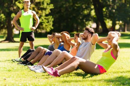 lifestyle: フィットネス、スポーツ、友情、健康的なライフ スタイル コンセプト - 幸せな 10 代の友人やスポーツマン行使してブート キャンプで腹筋運動を行