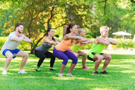 Fitness, Sport, Freundschaft und gesunden Lifestyle-Konzept - Gruppe von gl�cklichen Teenager-Freunde oder Sportler hockt am Boot Camp trainiert und tun