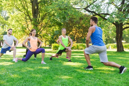 warm up exercise: fitness, sport, friendship and healthy lifestyle concept - group of happy teenage friends or sportsmen exercising and doing lunge at boot camp Stock Photo