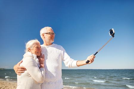 seniors: la edad, los viajes, el turismo, la tecnolog�a y el concepto de la gente - feliz pareja de ancianos con el tel�fono inteligente en el palillo selfie toma el cuadro en la playa de verano