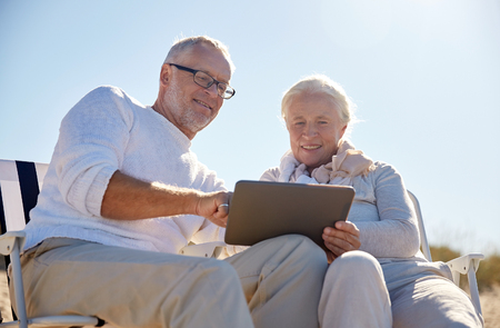 computer age: family, age, travel, tourism and people concept - happy senior couple with tablet pc computer resting in folding chairs on summer beach Stock Photo