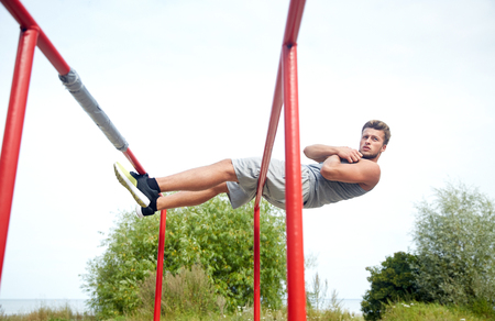 calisthenics: fitness, sport, exercising, training and lifestyle concept - young man doing sit up on parallel bars in summer park