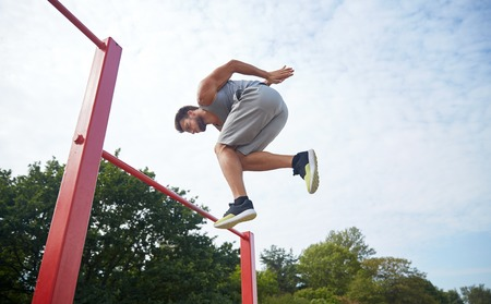 calisthenics: fitness, sport, exercising, training and lifestyle concept - young man jumping on horizontal bar outdoors