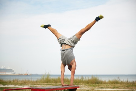 calisthenics: fitness, sport, training and lifestyle concept - young man exercising on bench outdoors