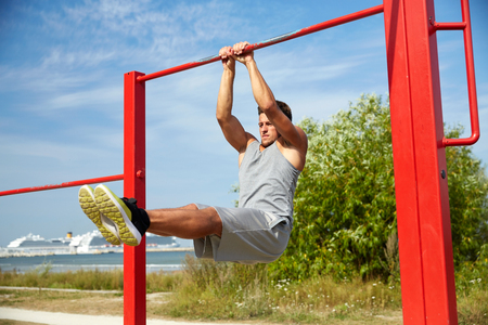 calisthenics: fitness, sport, exercising, training and lifestyle concept - young man doing abdominal exercise on horizontal bar in summer park