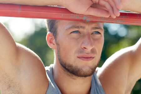 fitness training: fitness, sport, training and lifestyle concept - young man exercising on horizontal bar outdoors