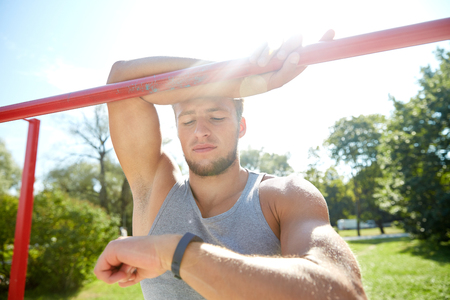 heartrate: fitness, sport, training and lifestyle concept - happy young man looking at heart-rate watch bracelet and exercising on horizontal bar in summer park
