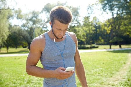 listening music: fitness, sport, technology and lifestyle concept - young man with smartphone and earphones listening to music at summer park Stock Photo
